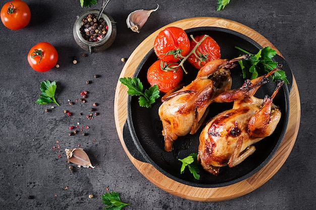 Baked quails in pan on a dark table.