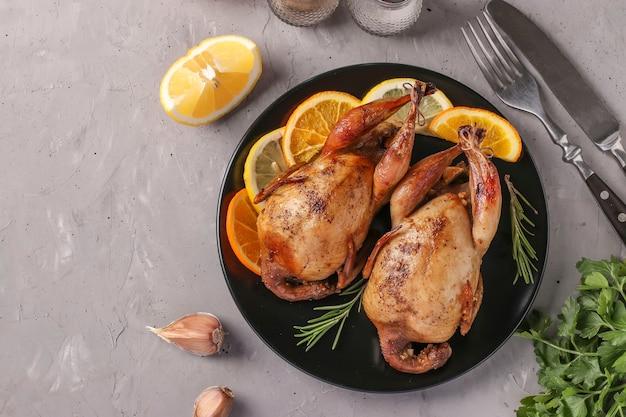 Запеченные перепела с лимоном и апельсином, подаваемые на темной тарелке на сером фоне, копией пространства, вид сверху