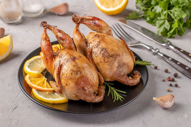 Baked quails with lemon and orange served on a dark plate