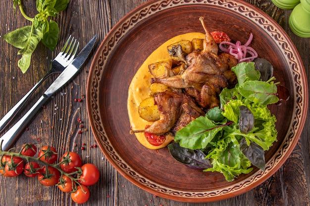 焼きウズラのポテト添え、サフランソースとグリーンサラダ添え、レストランの料理、クローズアップ、横向き