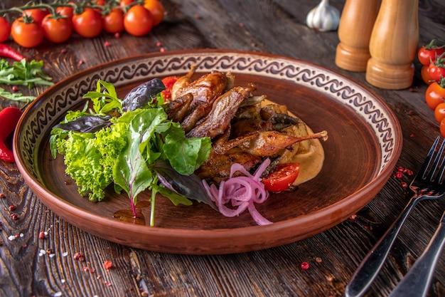 焼きウズラのポテト添え、サフランソースとグリーンサラダ添え、レストランの料理、横向き
