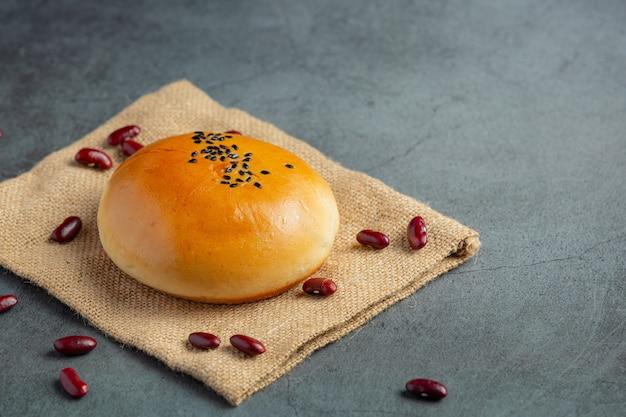 焼きたてのあんこパンを茶色の布の上に置きます