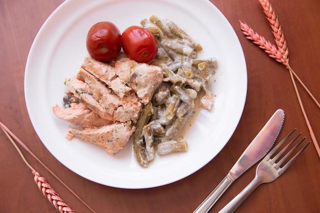 Запеченная красная рыба с зеленой фасолью. рыба с фасолью на тарелку. красные маринованные помидоры