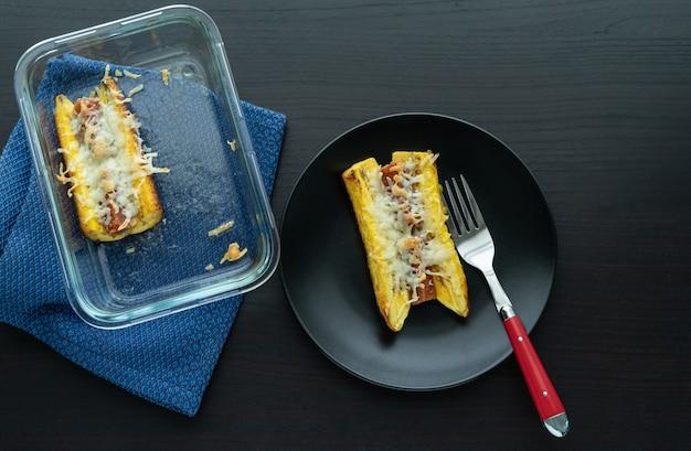 Запеченный спелый банан с гуавой и бутерброд с сыром на черной тарелке на черном деревянном основании. типичная колумбийская концепция еды. копировать пространство