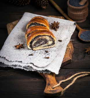 Baked roll with poppy seeds on a brown wooden board