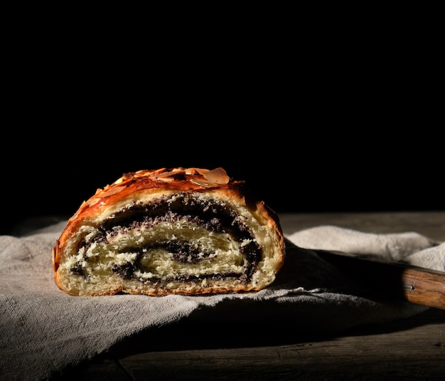Baked roll with poppy seeds on gray linen napkin