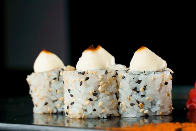 크림 치즈 클로즈업과 함께 흑백 참깨에 구운 롤. 스시 일본 요리.