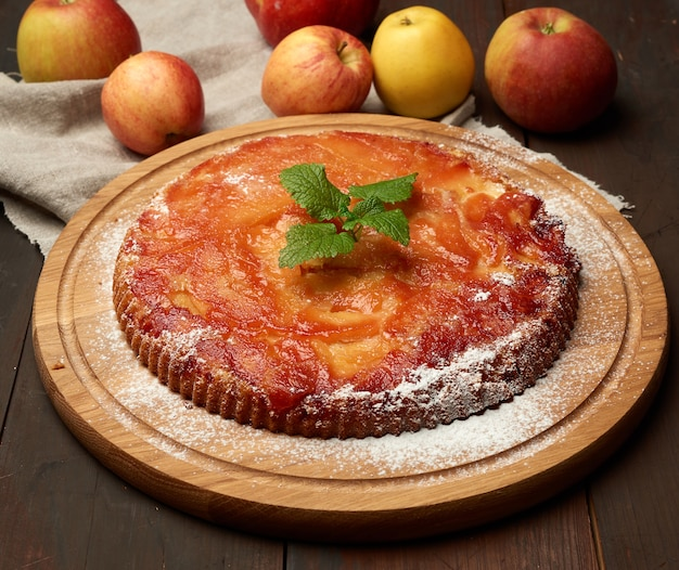 木の板と新鮮なリンゴ、茶色の木製テーブルに焼きたての丸いアップルパイ