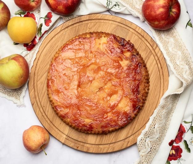木の板と新鮮なリンゴの焼き丸いアップルパイ、上面図、白いテーブル