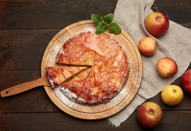 Запеченный круглый яблочный пирог на деревянной доске