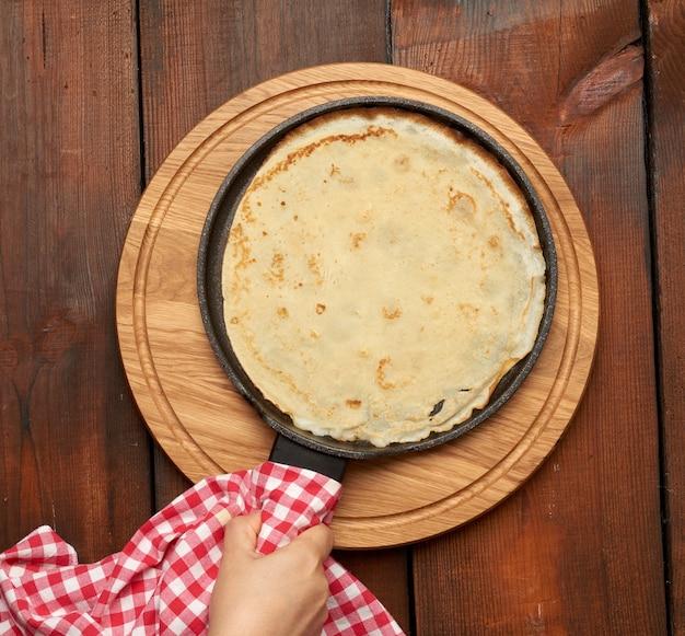 茶色の木製のテーブルに黒のフライパンで丸い大きなパンケーキを焼いた