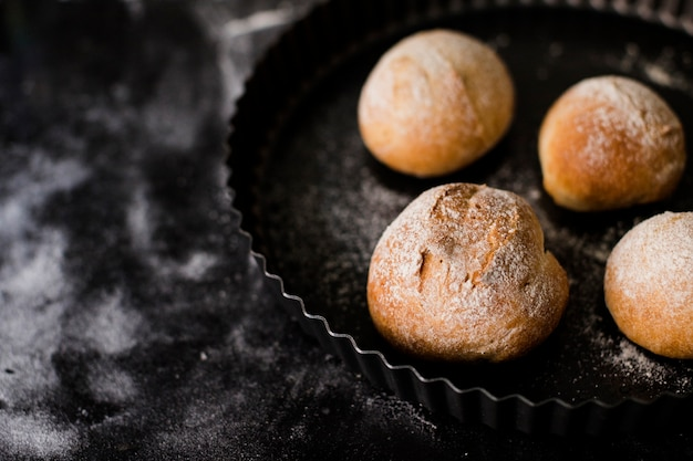 Baked round bread in plate on marble textured backdrop
