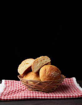 Baked round bun with sesame seeds, black space, home baking