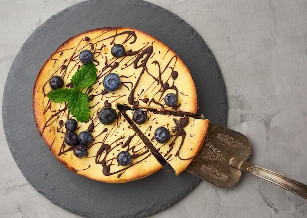 黒のプレートにカッテージチーズのキャセロール丸焼き