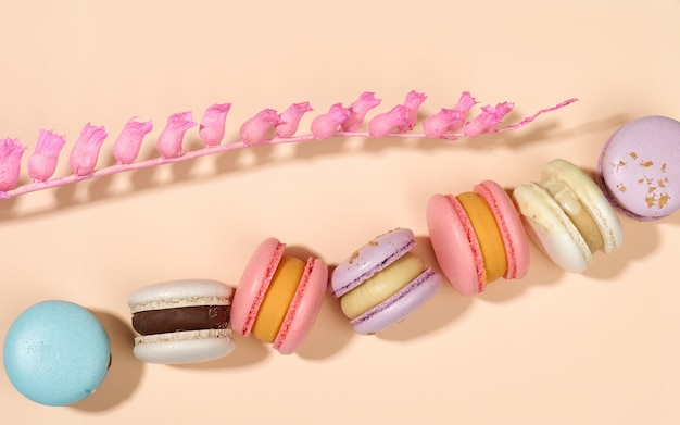 Baked round macarons on a beige background, delicious dessert, top view