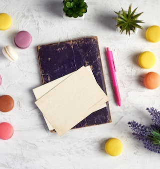 Baked round macarons, empty postcards, notebook, pink pen