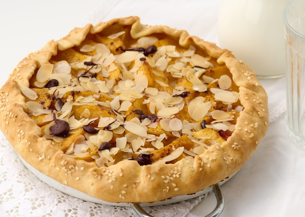 사과 조각이 있는 구운 원형 파이, 흰색 테이블에 아몬드 플레이크를 뿌린 위쪽 전망
