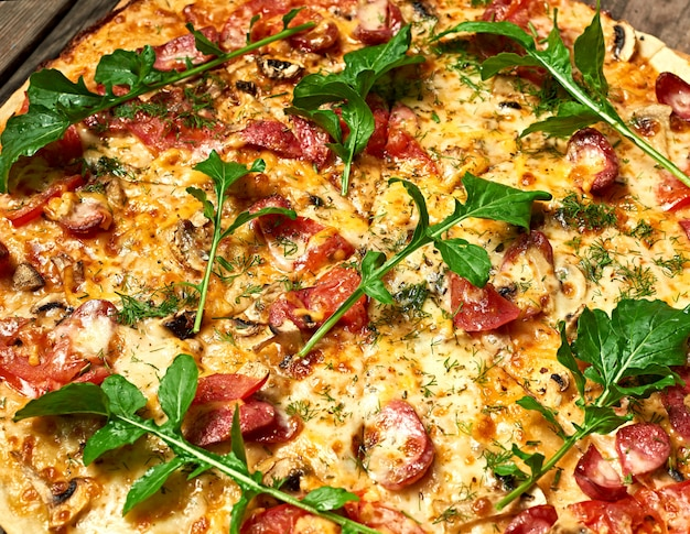 Baked round pizza with smoked sausages, mushrooms, tomatoes, cheese and arugula leaves