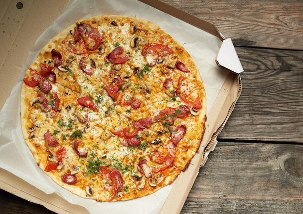 Запеченная круглая пицца с копчеными колбасками, грибами, помидорами