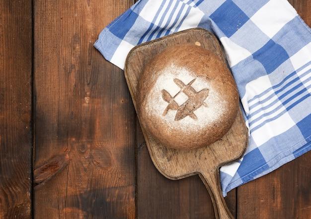 Запеченный круглый хлеб из ржаной муки на коричневой деревянной доске, вид сверху
