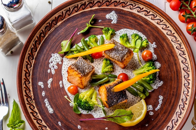 Baked salmon on chia sauce with broccoli, carrots, cherry tomatoes and green beans, horizontal photo, top view