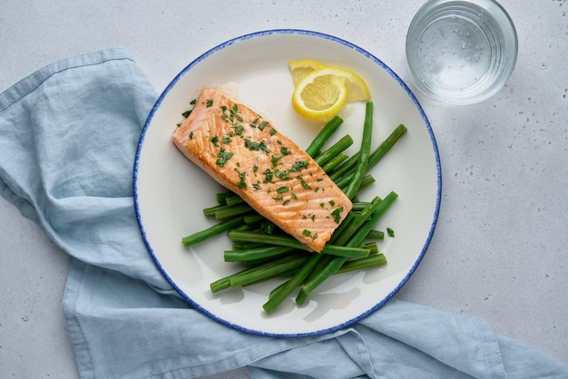 Baked salmon fillet with asparagus lemon parsley and glass of water pescetarian lunch