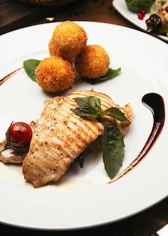 Запеченное филе лосося с картофелем и сырными рулетиками, а также микс овощей.