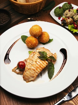 Baked salmon fillet with potatoes and cheese rolls, and vegetables mix.