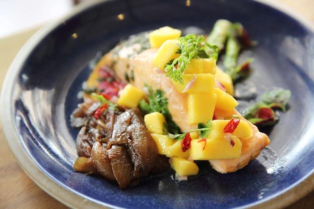ローズマリー、レモン、マンゴーを添えた焼き鮭の切り身