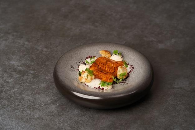 중국 콜리 플라워와 크림 소스를 곁들인 구운 연어 생선 필레