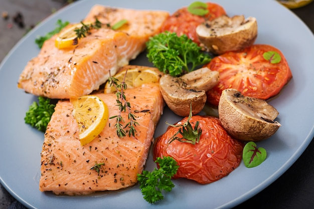 Baked salmon fish fillet with tomatoes, mushrooms and spices. diet menu.