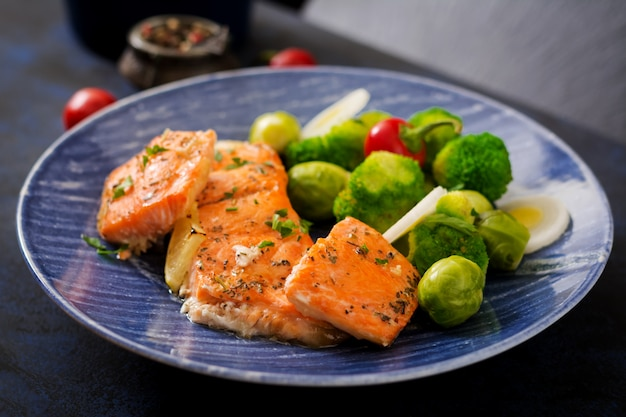 Baked salmon fish garnished with broccoli and brussels sprouts with leek. fish menu.