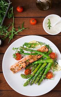 Запеченный лосось с гарниром из спаржи и помидоров с зеленью.