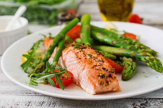 Salmone al forno guarnito con asparagi e pomodori alle erbe