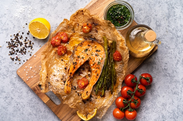 Baked salmon steak on parchment with vegetables, asparagus, tomatoes on a gray table.