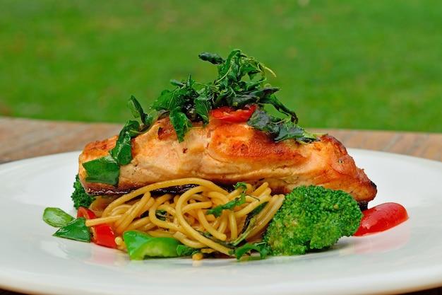 Baked salmon steak with spaghetti on white plate