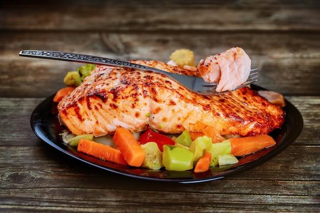 Запеченный лосось с азиатскими жареными овощами на черной тарелке с вилкой.