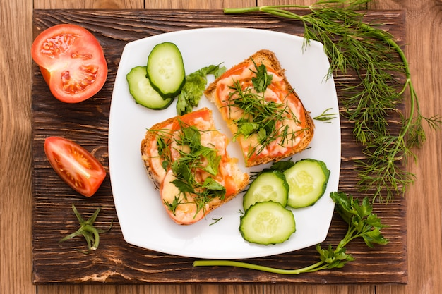 Baked sandwiches with tomato, cheese and greens and sliced vegetables. top view