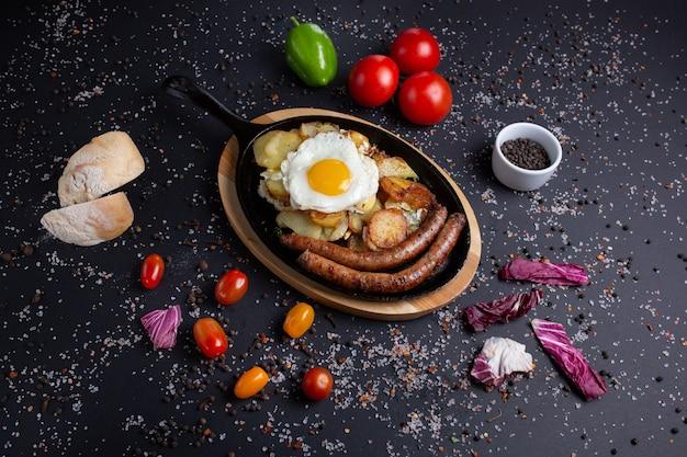 ジャガイモと揚げ卵を添えた焼きソーセージ、赤トマト、パン、赤ピーマン、ブロッコリーを添えた黒