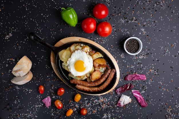 Запеченные сосиски с картофелем и яичницей подаются ресторанно, на черном с красными помидорами, хлебом, красным зеленым перцем и брокколи