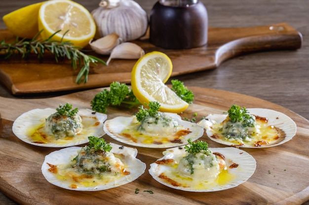 Baked scallops with cheese on a wooden cutting board