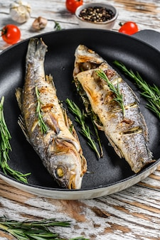 Baked sea bass fish, grilled seabass. white wooden background. top view.