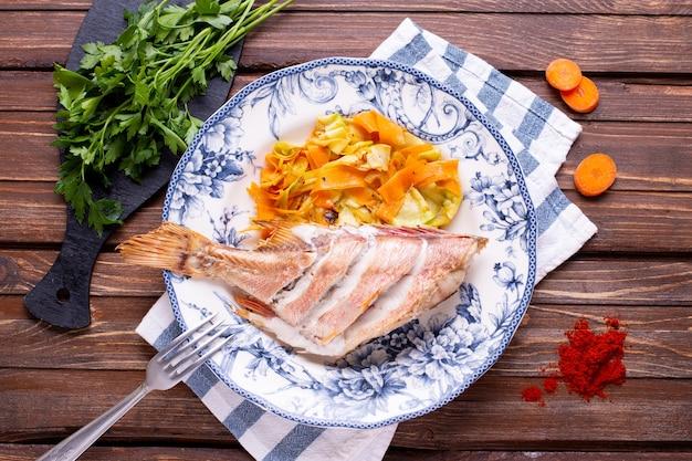 Запеченный морской окунь с овощами на столе