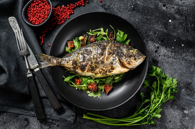 Baked sea bream fish with arugula salad and tomatoes. black background. top view