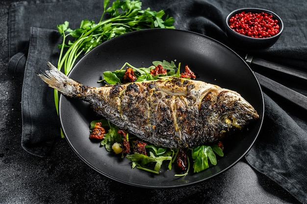 Baked sea bream fish with arugula salad and tomatoes. top view