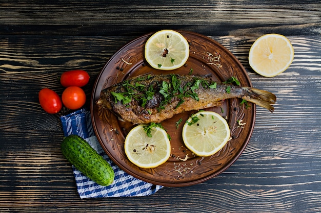 Baked sea fish with vegetables on surface