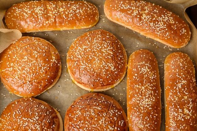 Запеченные булочки с кунжутом на коричневой пергаментной бумаге, ингредиент для гамбургера, вид сверху