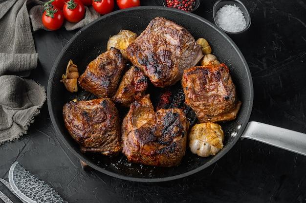검은 돌 배경에 구운 짧은 쇠고기 갈비 세트