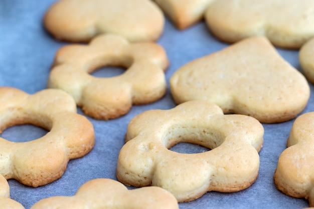 Запеченное песочное печенье в виде цветов и сердечек на противне с пергаментной бумагой, только что вынутом из духовки. чайная закуска на завтрак. выборочный фокус. крупным планом вид