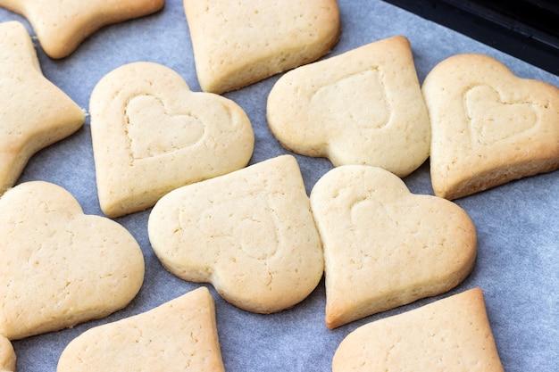 Печенье песочное в форме сердечек на противне с пергаментной бумагой